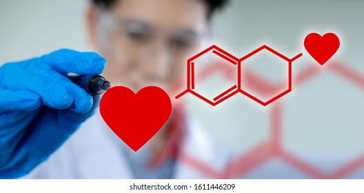A male scientist is writing a formula for the heart chemistry in love on Valentine's Day.