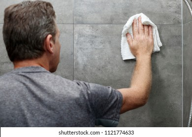 Male scrubbing a home bathroom gray tile shower wall with his hand holding a wet white cotton rag. White cotton cloth being used by an older caucasian man to clean a bathroom shower gray tile wall.