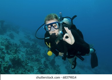 Male scuba diver gives OK sign in clear blue water