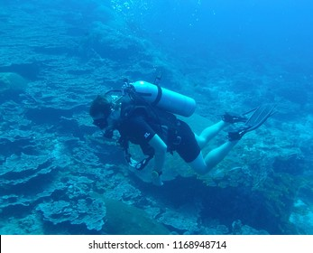 Male scuba diver holding a photography camera swimming under the water of Thai Indian Ocean in Similan Islands