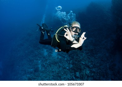 male scuba diver swims in clear blue water and makes the OK sign
