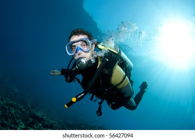 male scuba diver underwater with sunball