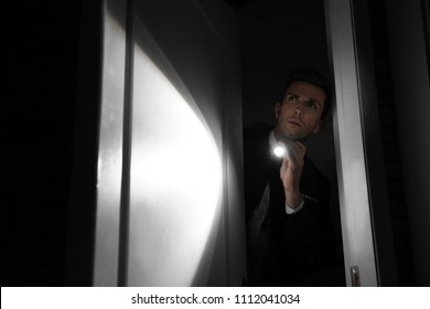 Male security guard with flashlight in dark room