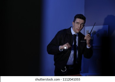 Male security guard with flashlight and portable radio transmitter in dark room
