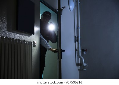 Male Security Guard Searching With Flashlight At Industry