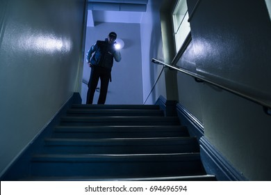 Male Security Guard Searching On Stairway With Flashlight