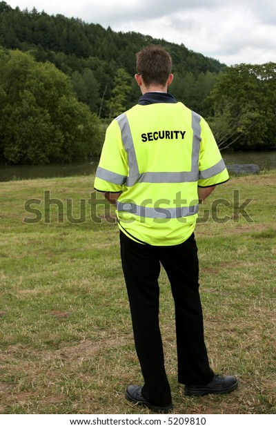 Male security guard standing alone in rural countryside. Rear view.