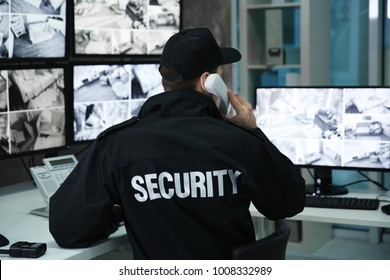 Male security guard talking by telephone in surveillance room