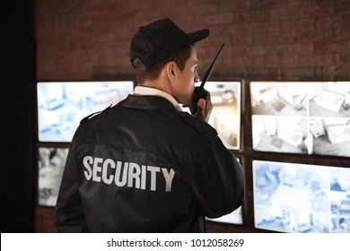 Male security guard using radio transmitter in surveillance room