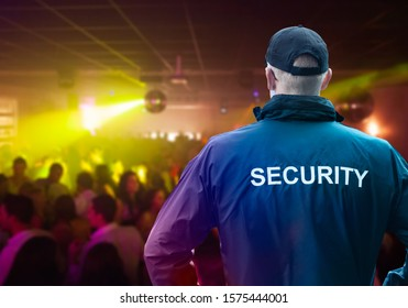 Male Security Officer Wearing Cap Standing In Night Club With His Hands On Hips