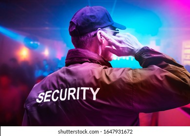 Male Security Officer Wearing Cap Trying To Listen Something On Earphones In Night Club