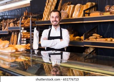 Male seller is demonstrating assortment of bakery.