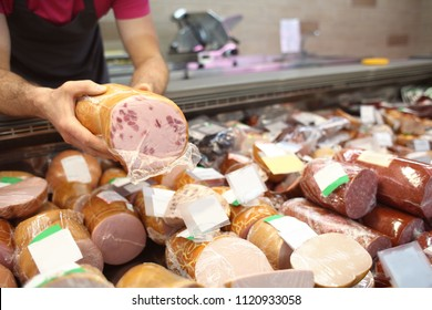 Male seller holding piece of deli meat in butcher shop