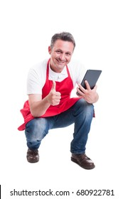 Male seller or merchandiser using digital tablet at store and showing like sign