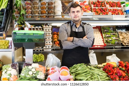 male seller showing assortment of fruits and vegetables in the grocery shop