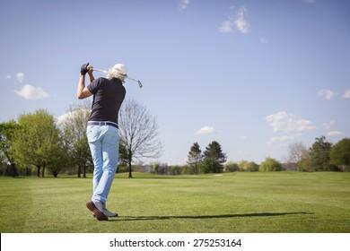 Male senior golf player hitting ball on fairway.