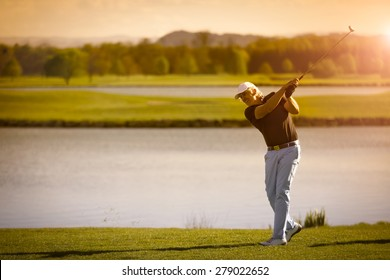 Male senior golf player swinging golf club with lake in background at sunset with copyspace.