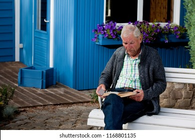 male senior with white hair in leisure wear with grey cardigan and blue jeans sits relaxed in the garden on a white  bank in front of an idyllic blue Pavillon and reads a book