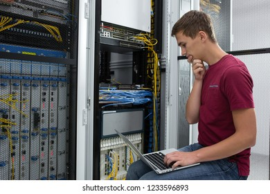 Male Server Engineer Works on a Laptop in Large Data Center.
