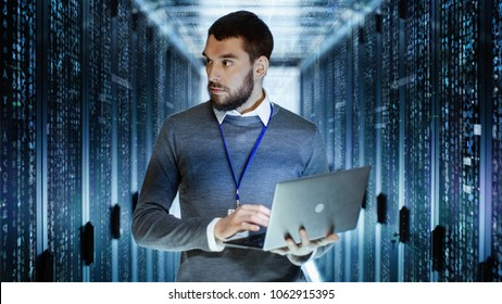 Male IT Server Technician Specialist Holds Laptop and Looking on Raining Script Code in Rack Sever Cabinet. He is Standing in Data Center.