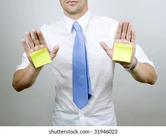 Male in shirt and tie holds hands out with post-it on palms