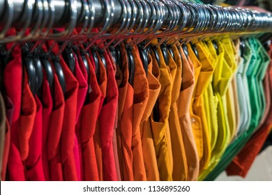 Male men's shirts sorted in color order on hangers on a thrift shop or wardrobe closet rail