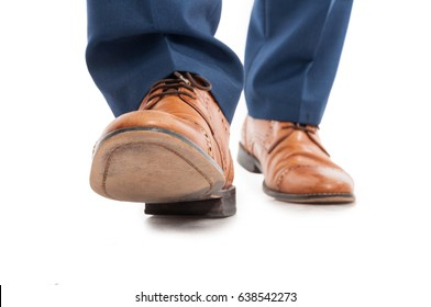 Male shoes and trousers in walking position in close-up on white background
