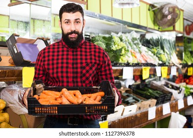 Male shop assistant demonstrating carrots in grocery shop