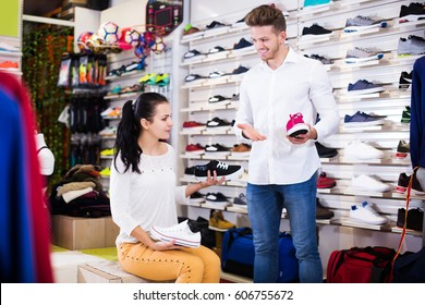 Male shop assistant helping customer to choose sneakers in sports store