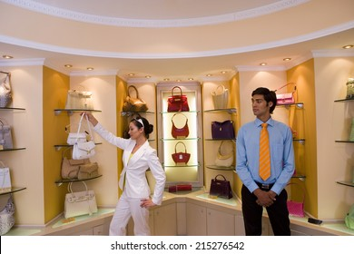 Male shop assistant watching woman shopping for designer handbags in glamorous boutique