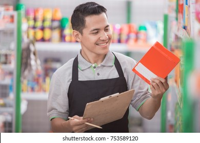 male shopkeeper checking the quality of the product at supermarket
