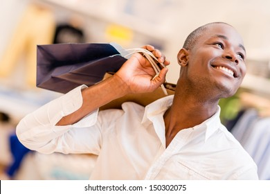 Male shopper holding shopping bags looking very happy