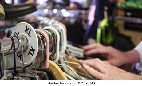 Male shopper looking through clothing on racks in extra large sizes