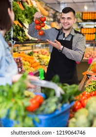 Male shopping assistant helping customer to buy fruit and vegetables in grocery shop