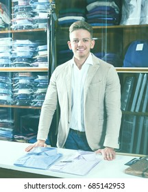 Male shopping assistant offering various shirts in mens cloths store