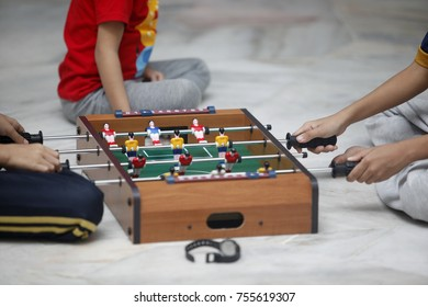 Male siblings having fun together playing indoor table football or fossball