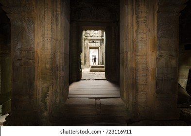 A male silhouette appears in the perspective of a corridor around the historical temple of Angkor Wat in Angkro, Cambodia.