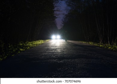 Male silhouette at the edge of a dark mountain road through the forest in the night. Man standing on the road against the car headlights. The car on the roadside. Mystery concept. Soft focus, filter.