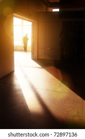 Male silhouette in empty interior looking in window, lit by dramatic sunlight.