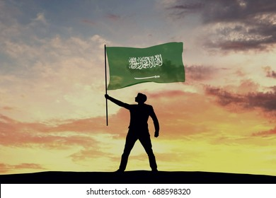 Male silhouette figure waving Saudi Arabia flag. 3D Rendering