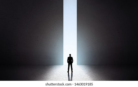 Male silhouette in front of huge opening concrete doors with blue light opening, panorama, copy space