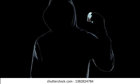 Male silhouette holding packet with pills, drug trafficking crime, lifestyle