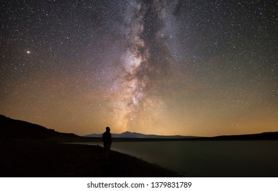 Male silhouette standing on the shore. Beautiful galaxy Milky Way and the lake.