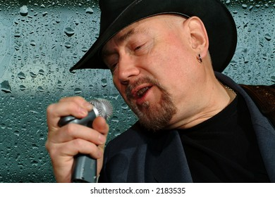 male singer with glass full of water drops on the background