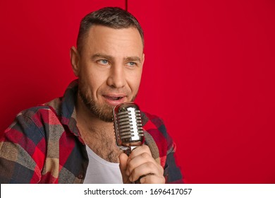 Male singer with microphone near color wall