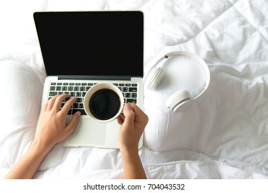 Male sitting on white bed surfing internet or working on laptop and listening to musical media online with wireless headphone and drink coffee in morning relax mood. Music and Lifestyle Concept.