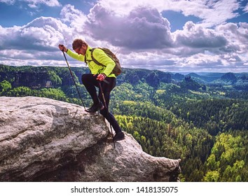 Male skarner climb within mountain trail with trekking poles and backpack. Man with ultralight equipment stay for e moment on exposed view point