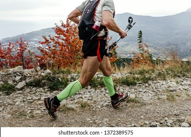 male skarner running mountain trail with trekking poles and backpack with water bottle