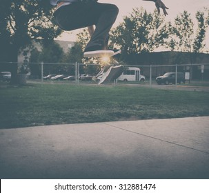 male skate boarder doing a kick flip at a skate park with a toned instagram filter during sunrise or sunset