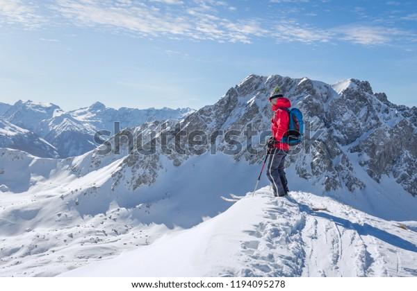 Touriste de ski masculin jouissant de la vue sur un sommet dans les alpes